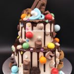 Drip Cake - 2 Tier chocolate drip cake with fondant pacifier, chocolates, chocolate cookies and colourful candy balls. Singapore Customized Cakes