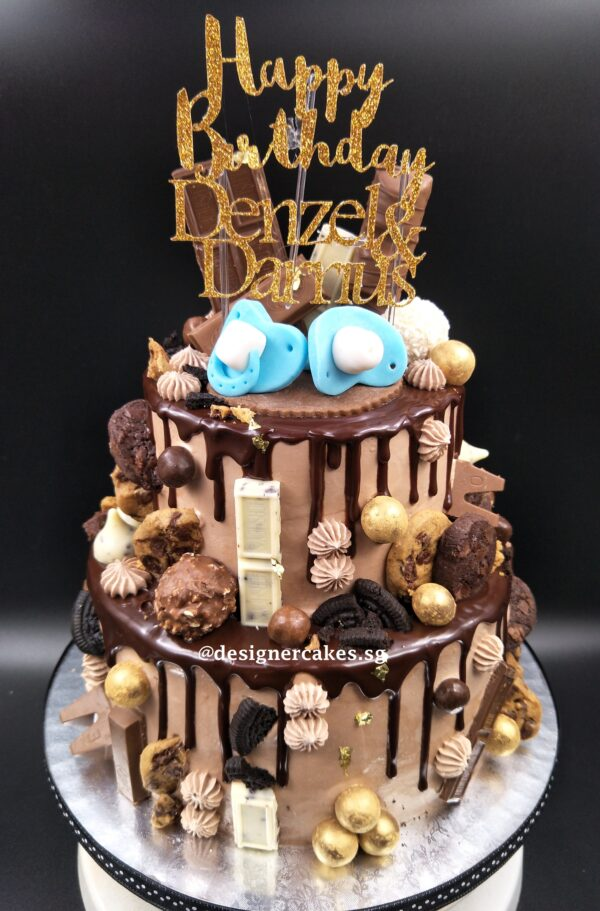 Drip Cake - 2 Tier chocolate drip cake with fondant pacifier, chocolates, chocolate cookies, gold balls, edible gold leaf and customized name cake topper. Singapore Customized Cakes