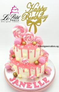 Drip Cake - 2 Tier pink and white drip cake with lollipop, macarons and gold balls. Singapore Customized Cakes