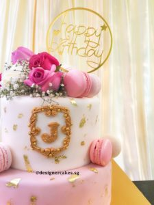 2 Tier White and Pink Themed Fondant Cake with Real Gold Flakes, Fresh Roses & Baby Breathe and Pastel Tones of Macarons